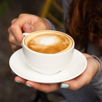 Primo piano della tazza di caffè della tenuta della donna