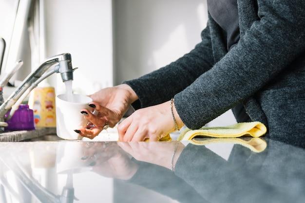Primo piano della tazza di lavaggio della mano di una femmina