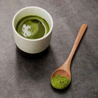 Primo piano della tazza di tè di matcha con il cucchiaio di legno