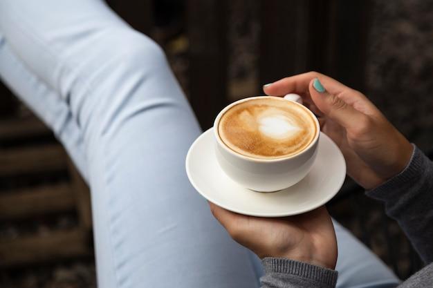 Primo piano della tazza e del piatto di caffè della tenuta della donna