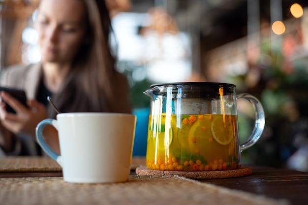 Primo piano della tazza e teiera di vetro con il tè dell'olivello spinoso con il limone e le erbe, donna con lo smartphone su vago