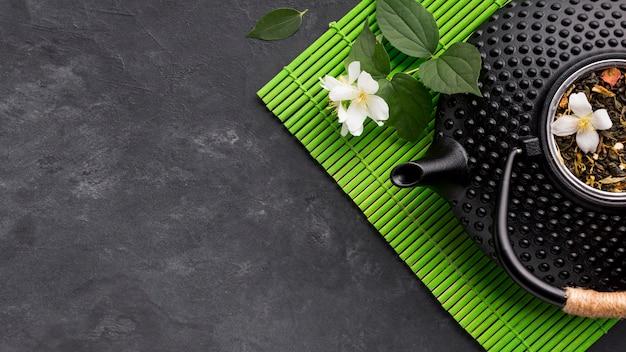 Primo piano della teiera nera con l'erba secca del tè su placemat verde sopra fondo strutturato