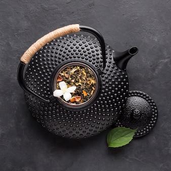 Primo piano della teiera nera con l'erba secca del tè