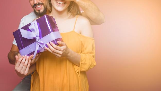 Primo piano della tenuta delle coppie che ha avvolto il contenitore di regalo porpora