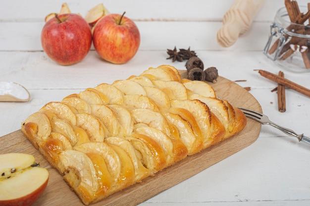 Primo piano della torta di mele con pasta di brioche sul tagliere di legno. natura morta sulla tavola di legno bianca.
