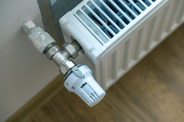 Primo piano della valvola del radiatore di riscaldamento per una regolazione confortevole della temperatura sul radiatore in metallo sulla parete interna.