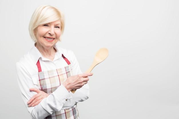 Primo piano della vecchia donna che ama trascorrere il suo tempo libero in cucina e cucinare cibi gustosi. prepara un pasto delizioso.
