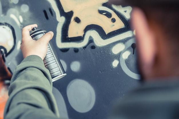 Primo piano della vernice di spruzzatura della mano di un uomo sulla parete dei graffiti