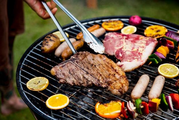 Primo piano delle bistecche dei barbecue sulla griglia dei carboni