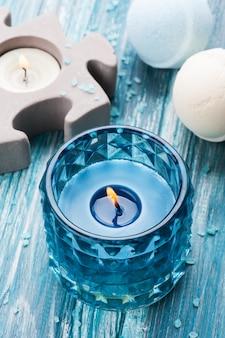 Primo piano delle bombe da bagno con la candela accesa blu