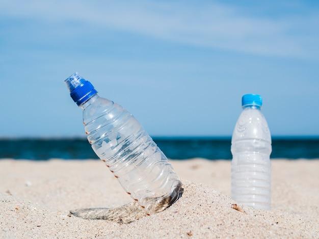 Primo piano delle bottiglie di acqua di plastica bloccate in sabbia alla spiaggia