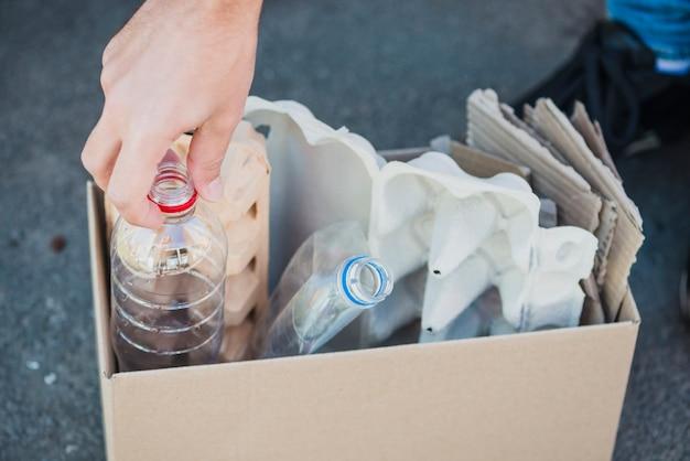 Primo piano delle bottiglie di plastica e del cartone dell'uovo nella scatola