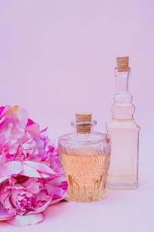 Primo piano delle bottiglie e dei fiori dell'olio essenziale sul contesto viola