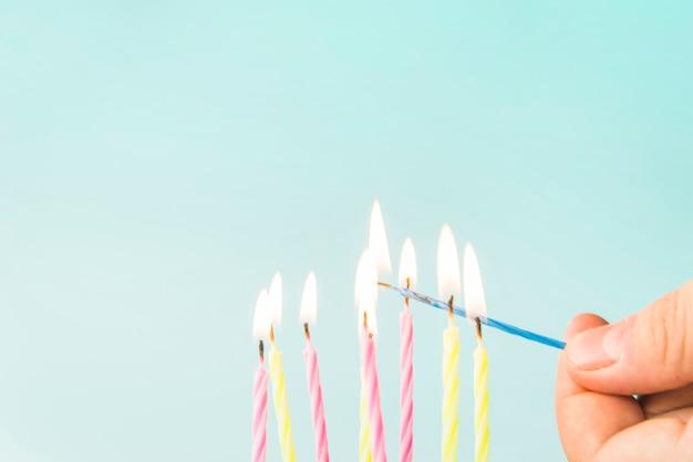 Primo piano delle candele di un fulmine della persona contro fondo blu