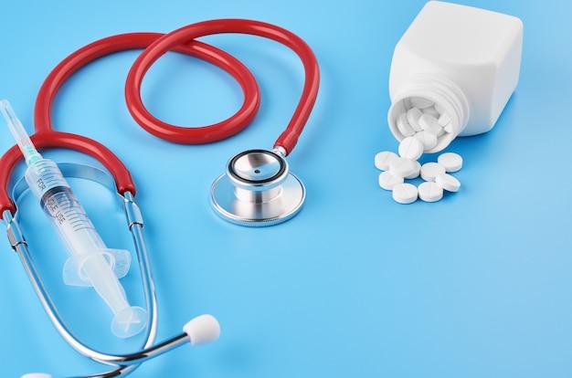 Primo piano delle capsule delle compresse delle pillole. su uno sfondo blu, un barattolo di medicina. su uno sfondo blu, un barattolo di medicina e uno stetoscopio.