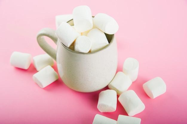 Primo piano delle caramelle gommosa e molle e spazio della copia su un rosa. marshmallow in una tazza di terracotta.