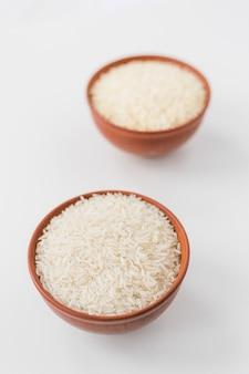 Primo piano delle ciotole di riso gelsomino crudo su carta da parati bianca