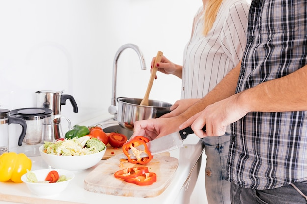 Primo piano delle coppie che preparano alimento nella cucina