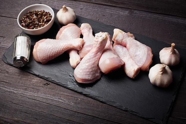 Primo piano delle coscie di pollo crude.