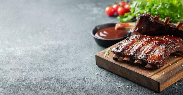 Primo piano delle costole di maiale grigliate con salsa barbecue.