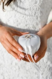 Primo piano delle fedi nuziali dell'oro legate con un nastro di seta bianco ad un contenitore di gioielli nelle mani della sposa, fuoco selettivo