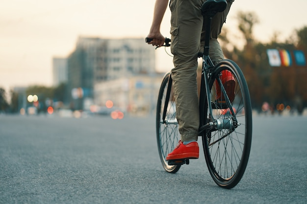 Primo piano delle gambe casuali dell'uomo che guidano bici classica sulla strada di città