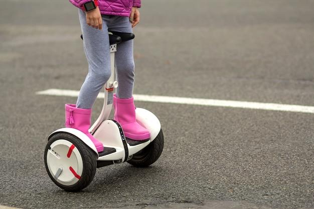 Primo piano delle gambe della ragazza del bambino in stivali di gomma rosa luminosi che guidano segway sulla via asfaltata soleggiata