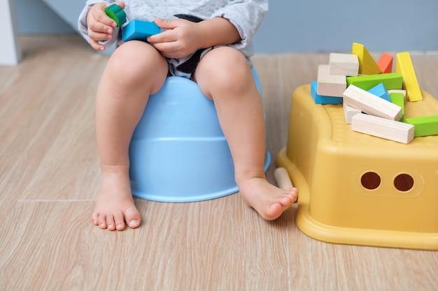 Primo piano delle gambe di piccola seduta asiatica sveglia del bambino del neonato di 18 mesi del bambino