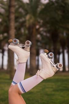 Primo piano delle gambe femminili di un pattinatore in pattini e calzini bianchi del rullo