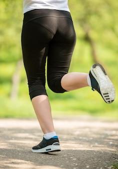 Primo piano delle gambe femminili in scarpe da ginnastica.