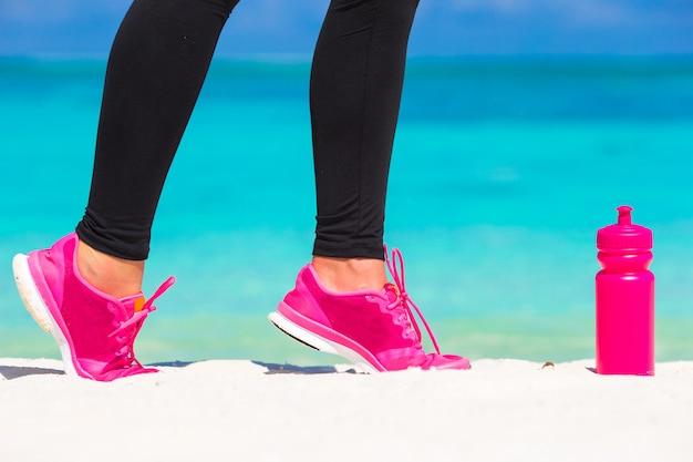 Primo piano delle gambe femminili in scarpe da tennis in esecuzione sulla spiaggia di sabbia bianca