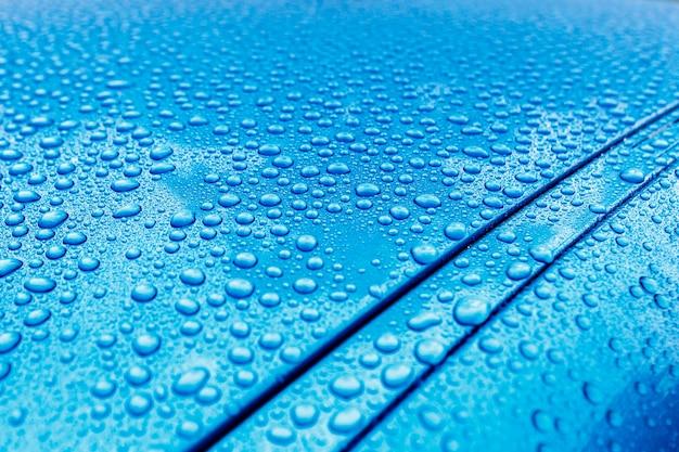 Primo piano delle gocce di pioggia su un corpo macchina turchese con effetto idrofobico