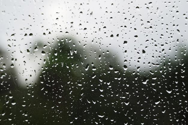 Primo piano delle gocce di pioggia su una finestra dopo una pioggia tropicale