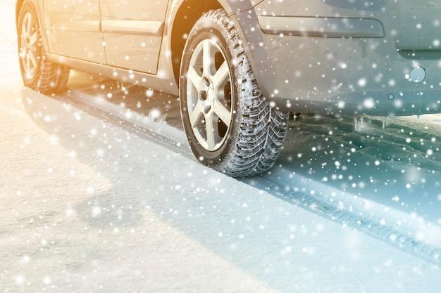 Primo piano delle gomme di gomma delle ruote di automobile nella neve profonda di inverno. concetto di trasporto e sicurezza.