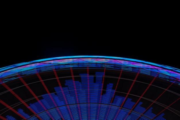 Primo piano delle luci al neon della ruota di meraviglia su fondo nero
