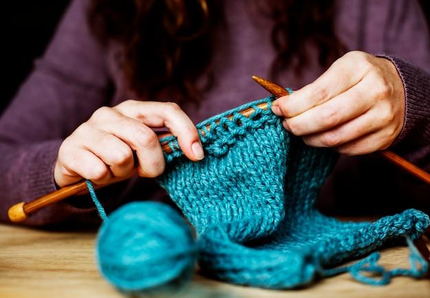 Primo piano delle mani a maglia sul tavolo di legno