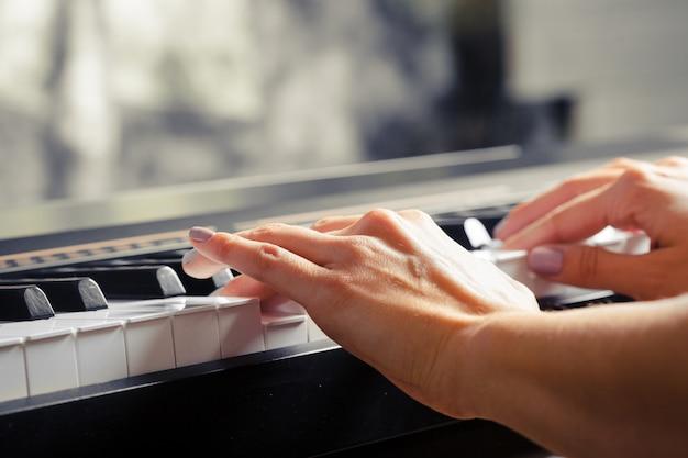 Primo piano delle mani che giocano il piano. concetto di musica e hobby