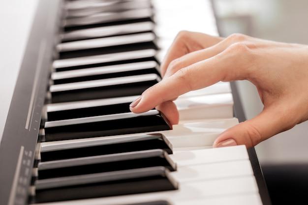 Primo piano delle mani che giocano piano. concetto di musica e hobby
