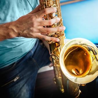 Primo piano delle mani che giocano sassofono