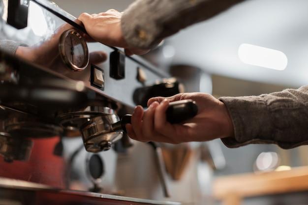 Primo piano delle mani che lavorano alla macchina del caffè