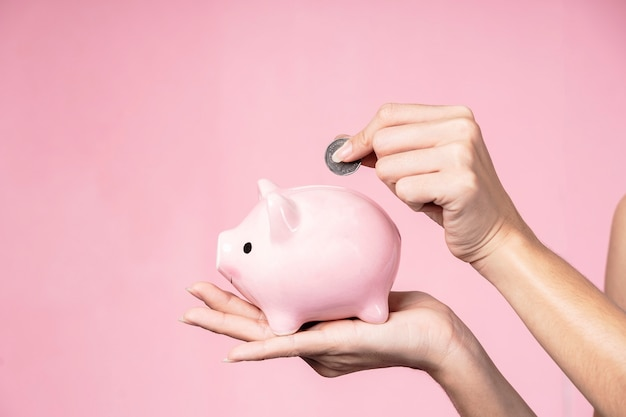 Primo piano delle mani che mettono moneta in un porcellino salvadanaio