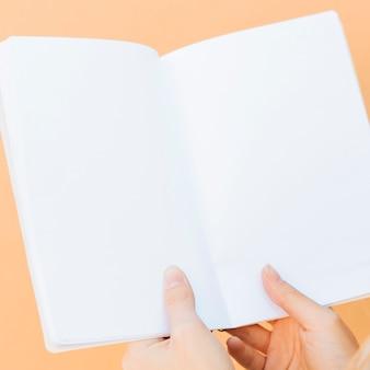Primo piano delle mani che tengono il libro bianco in bianco contro il contesto colorato