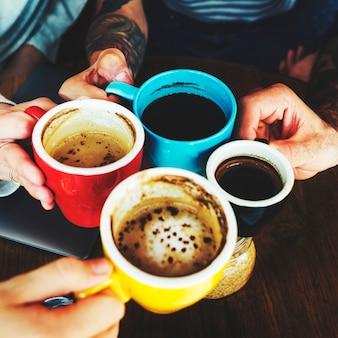 Primo piano delle mani che tengono insieme le tazze di caffè