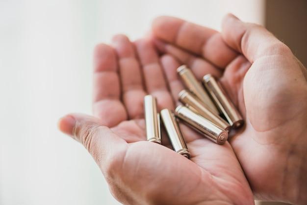 Primo piano delle mani che tengono le cellule della batteria