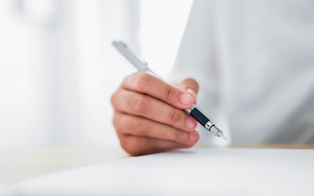 Primo piano delle mani che tengono penna e scrittura sul blocco note
