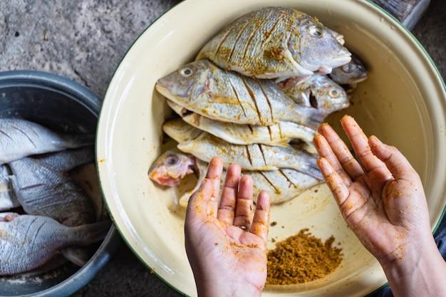 Primo piano delle mani con polvere di curcuma bagnata con pesce crudo. messa a fuoco selettiva.