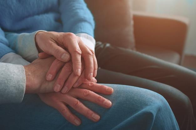 Primo piano delle mani degli anziani tenendoli insieme.