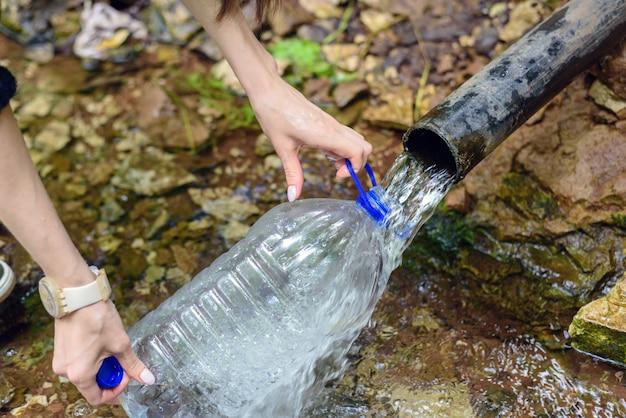 Primo piano delle mani degli uomini con una bottiglia di plastica, si riempie di acqua fresca pulita proveniente dalla sorgente, fonte sotterranea