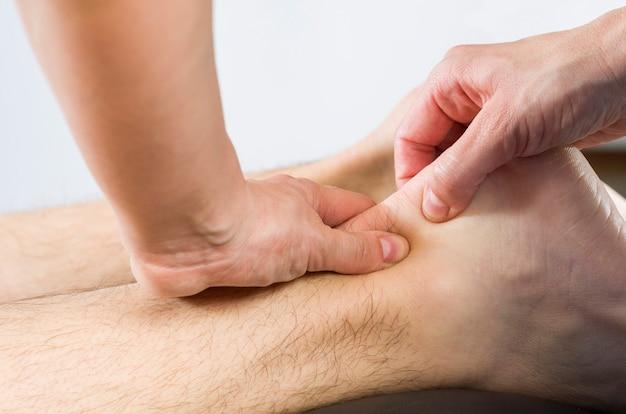 Primo piano delle mani del chiropratico / fisioterapista che fa massaggio del muscolo del vitello al paziente dell'uomo.