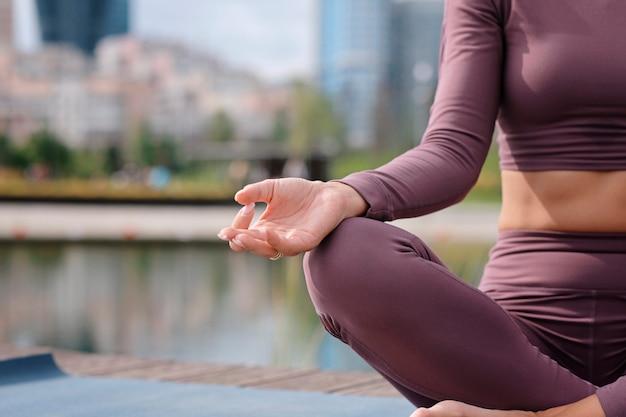 Primo piano delle mani del giovane ufficio yogi woman sittingriverbank in città, meditando con le dita in jnana mudra